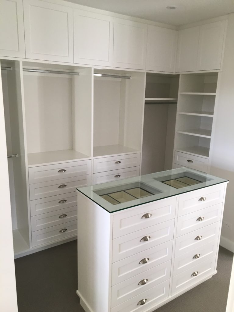 White walk in wardrobe drawer island