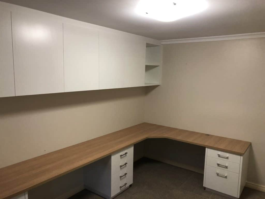 Office desk and overhead cupboards