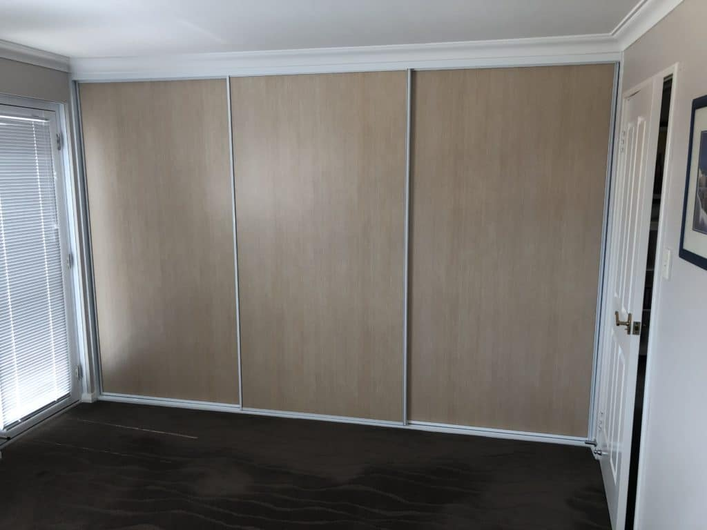 Sliding door wardrobe in wood grain look board